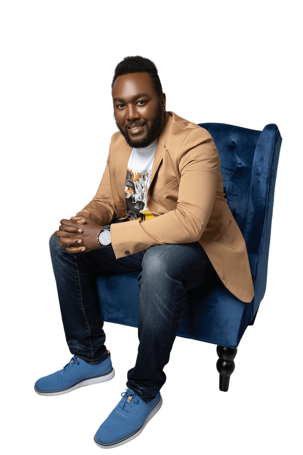Josh sitting in a blue chair with hands folded and smiling.